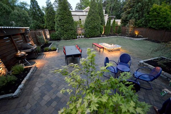 backyard living space with grill, outdoor furniture and tables, fire feature and landscaping