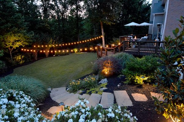 backyard with stone landscape stairs leading to grass living space with outdoor hanging string lights