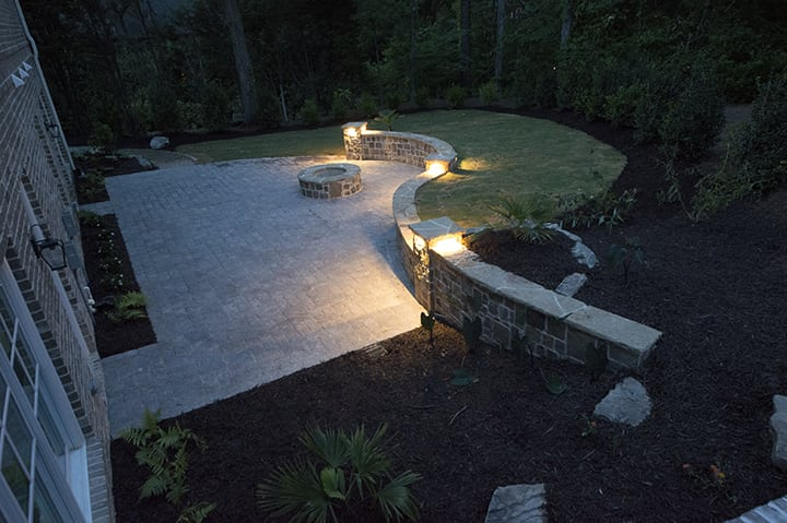stone backyard living space with fire pit and hardscaping with outdoor surface landscape lighting