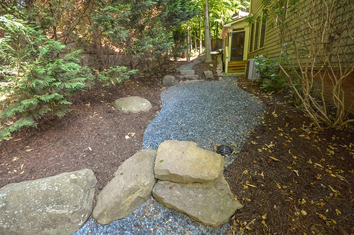 gravel and rock xeriscaping in backyard with fence and landscaping
