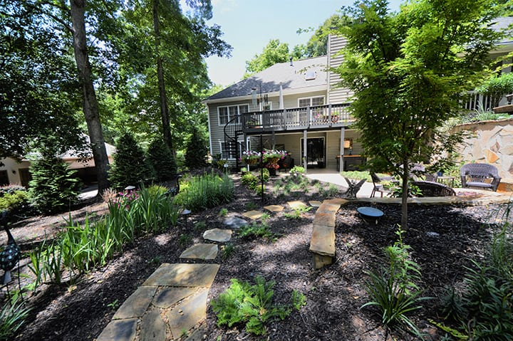 backyard with landscaping and softscaping for house with black back deck and outdoor living space