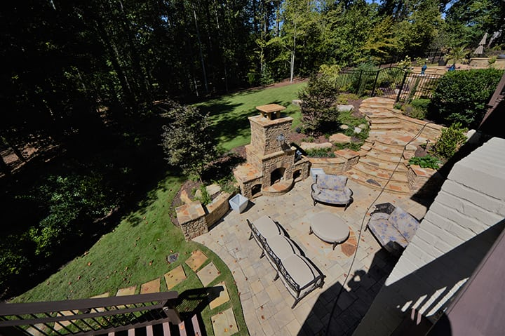 landscaped stone patio and outdoor living space with stone fire place and outdoor furniture
