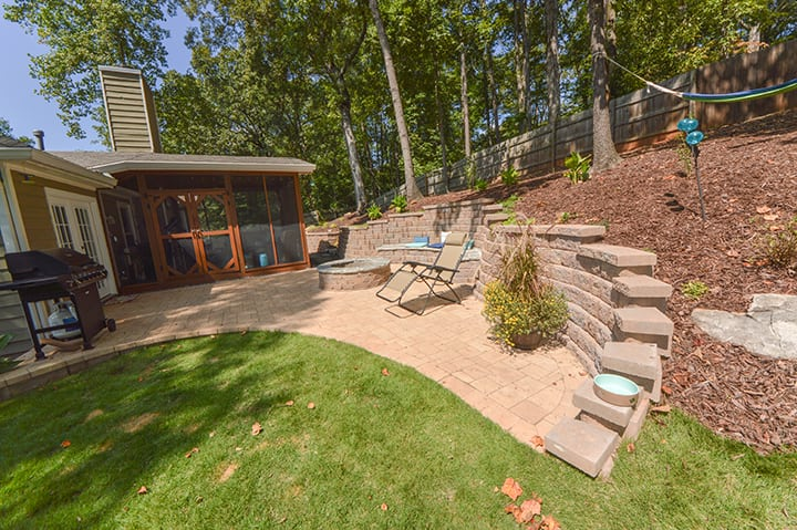 backyard summer landscape with stone wall, outdoor grill, and wooden fence