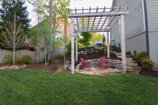 outdoor pergola structure with stone stairway in backyard with green grass and trees