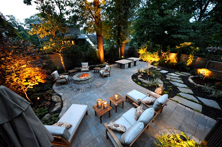 outdoor stone backyard living space with outdoor furniture and fire pit with outdoor landscape lighting