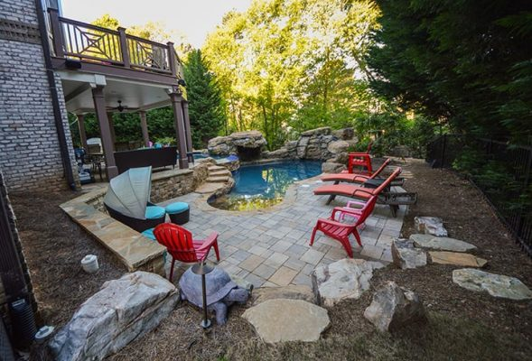 poolside hardscaping with red outdoor furniture and backyard deck and patio