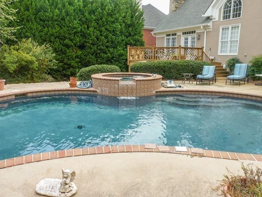 poolside view of pool with landscaping, brick hot tub and backyard wooden deck