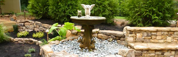 stone water fountain with landscaping and hardscaping design