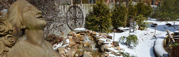 backyard stone statue with stone garden fountain and ever green trees covered in winter snow