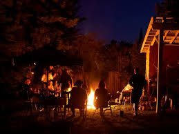 people sitting around fire pit during nighttime in the fall