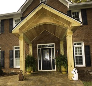 wooded portico on front of brick house with a black door and stone walkway