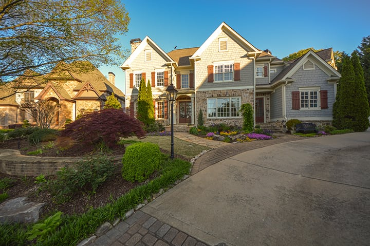 front yard landscaping with outdoor light post and stone walkway leading to house