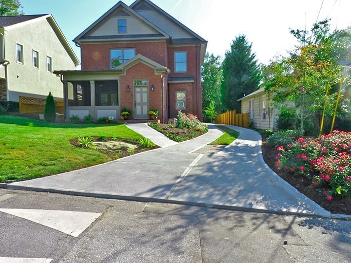 front yard landscaping design with driveway leading to brick house