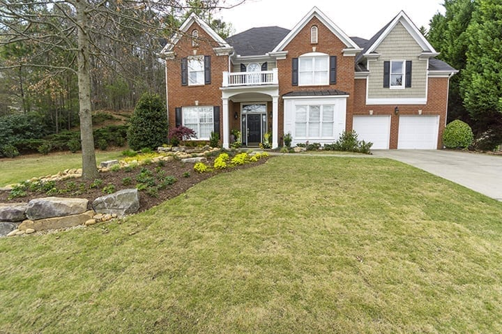 front yard of georgia brick home with green grass and landscaping design