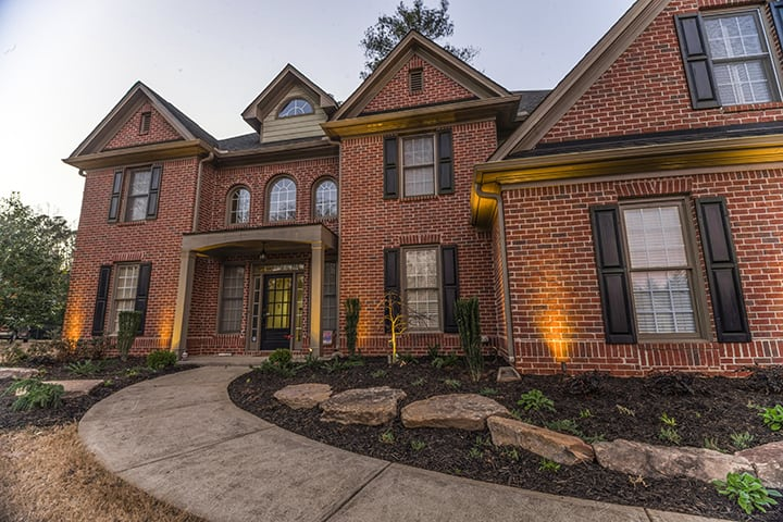 brick house with outdoor surface lighting design and concrete walkway to front door
