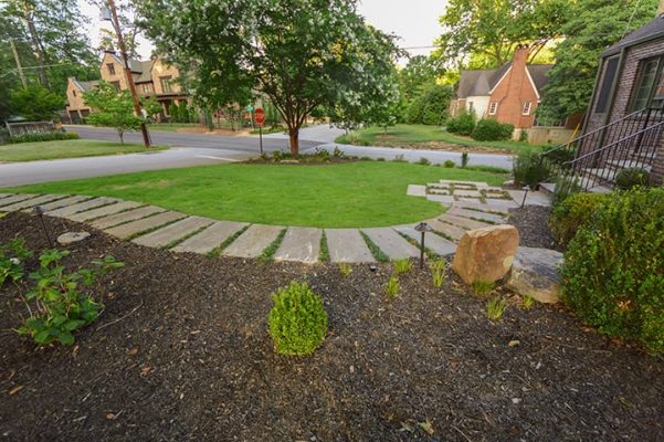 front yard stone landscape walkway leading from brick house to the street