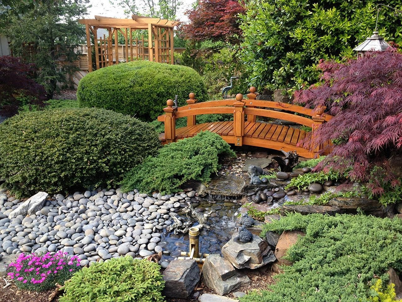 wooden bridge crossing over stone garden fountain with shrubberies and softscaping next to pergola