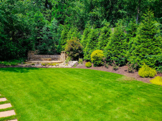 grass landscape with stone fire pit and outdoor living space atlanta