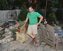 proud designer for Outdoor Makeover & Living Spaces in green shirt on backyard makeover project