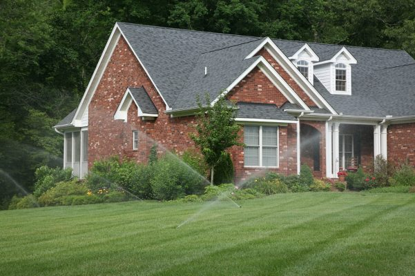 criss-crossing spraying lawn sprinkler irrigation system on grass yard of brick house