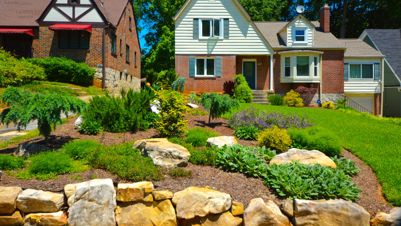 frontyard landscape of brick house with colorful plants and grass yard