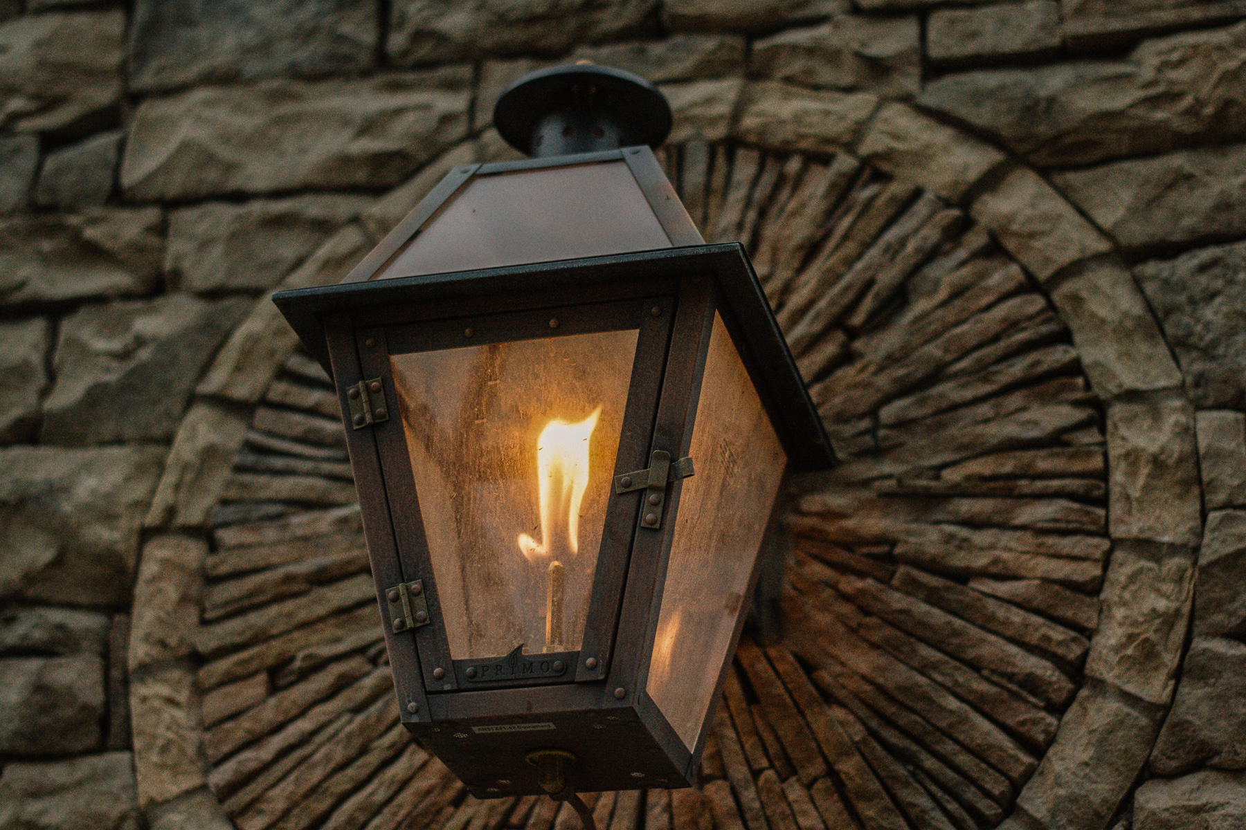 outdoor gas burning light fixture mounted on stone wall