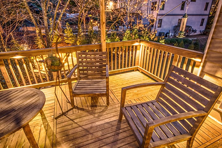 backyard living space wooden deck with surface lights and wooden chairs around table