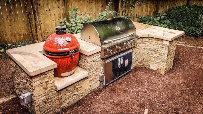 stainless steel grill and red smoker in outdoor stone kitchen
