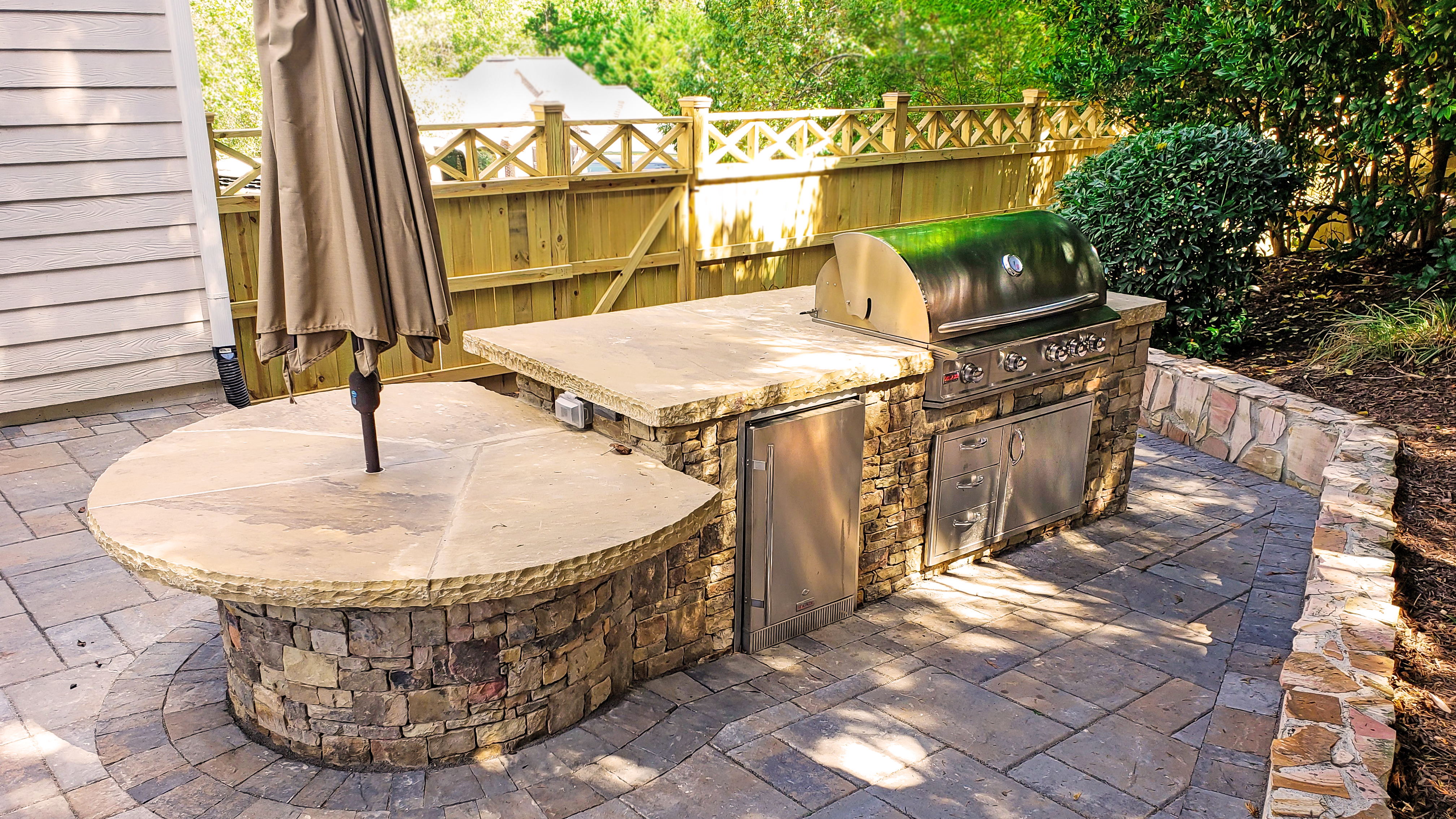 stone outdoor kitchen with steel grill and wooden privacy fence
