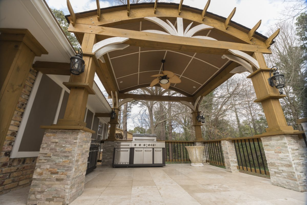 pergola with ceiling fan over stone patio with outdoor stainless steel grill