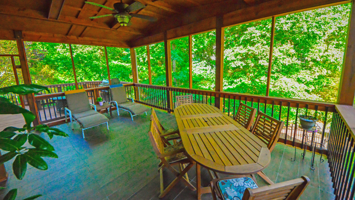 screened-in backyard porch with lounge chairs and wooden outdoor dining area