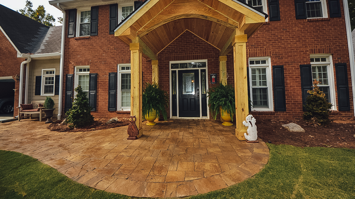 front door of brick house with wooden portico and hardscape walkway