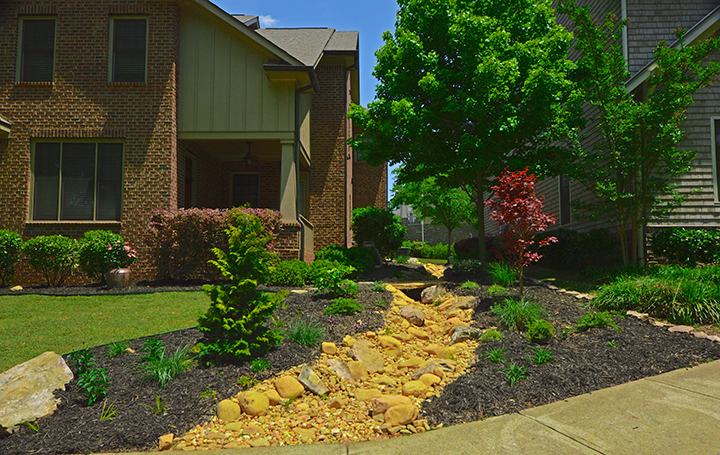 front yard with stone landscape drainage design