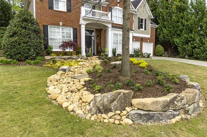 rock landscaping with trees and yellow flowers in front of brick house and green grass yard