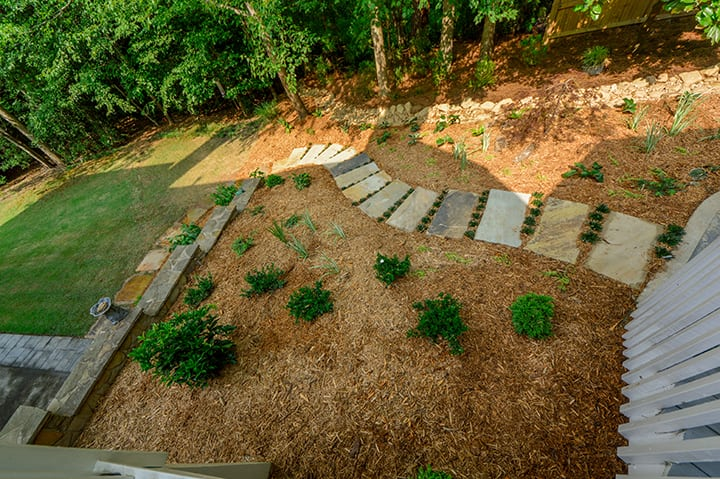 mulched backyard and stone pathway to green grass outdoor living space