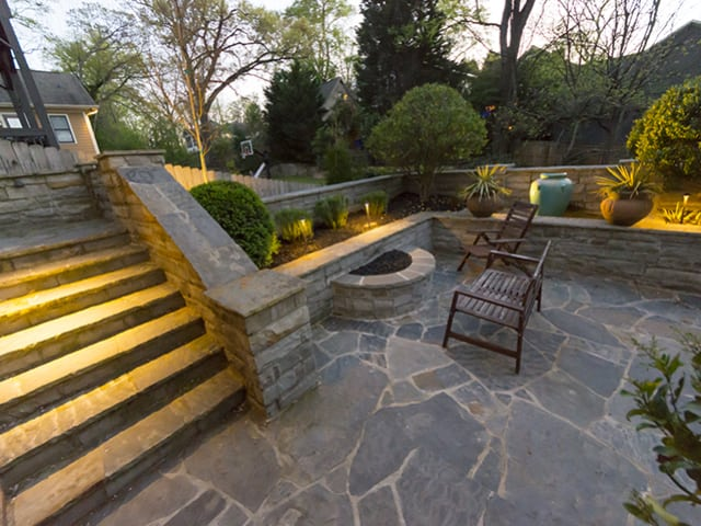 backyard stone stairway leading to outdoor patio with chairs and landscape lighting