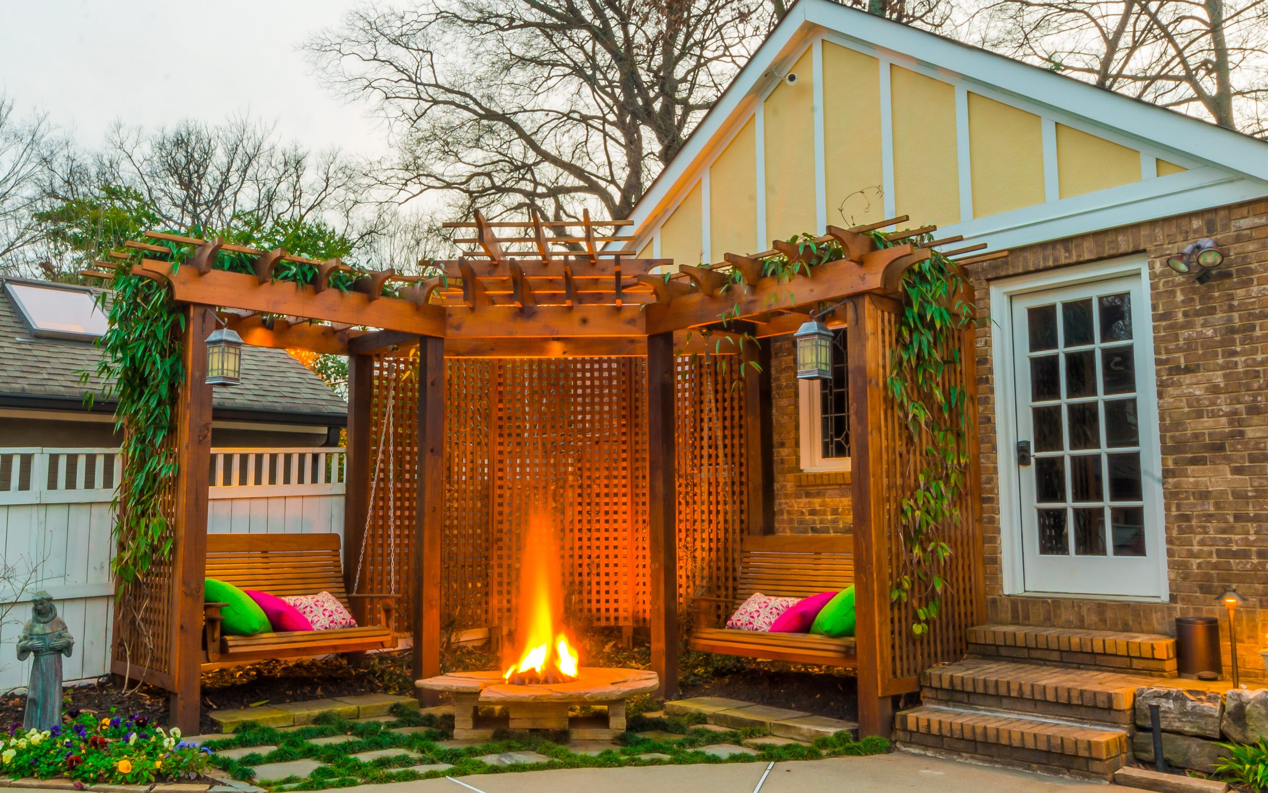 fire pit under pergola with wooden swings next to backyard guest house