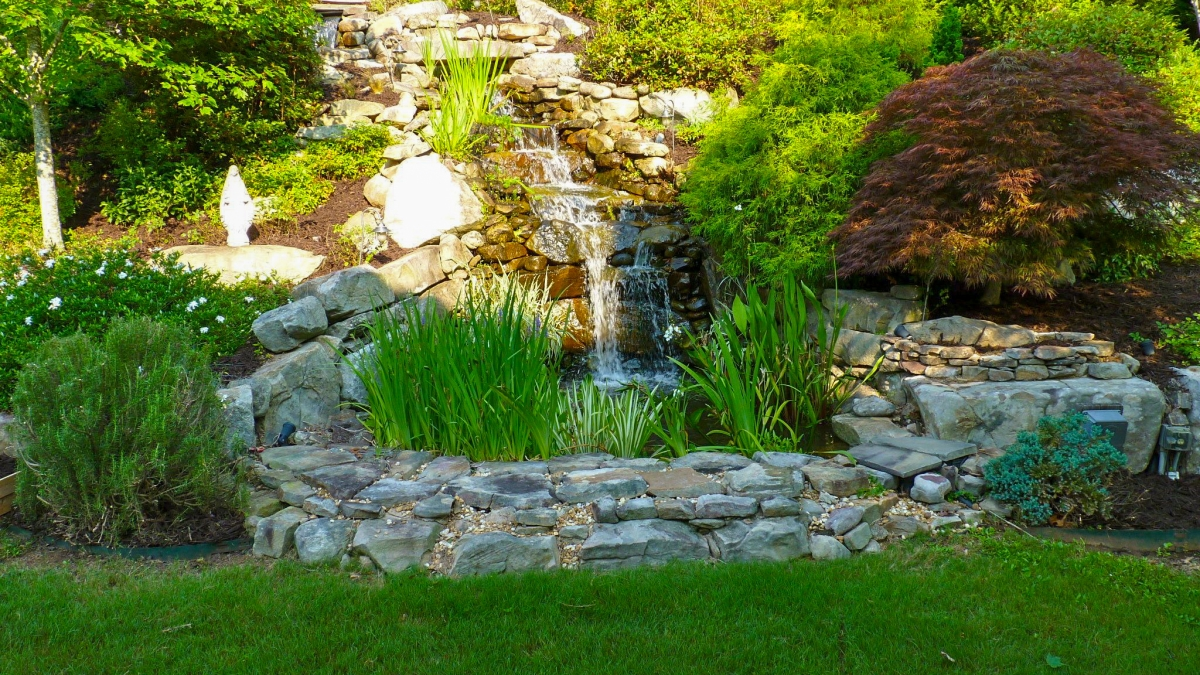 backyard stone waterfall with colorful landscaping