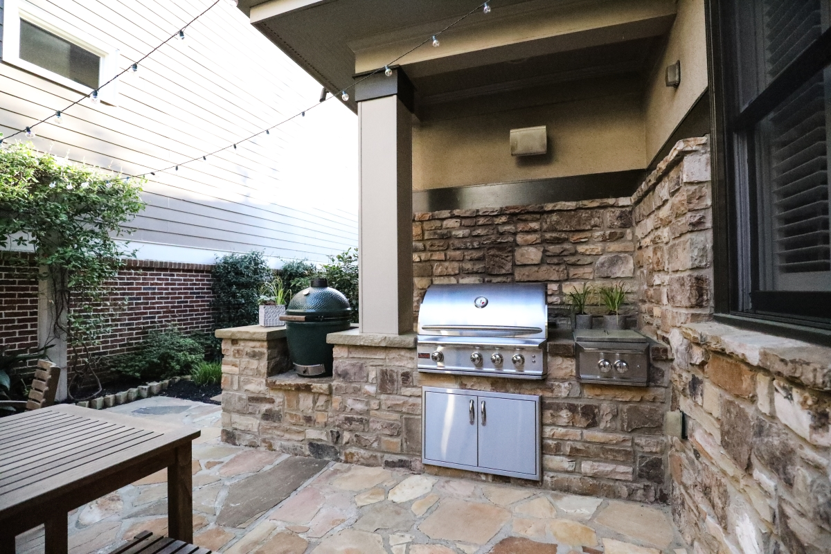 outdoor kitchen with green smoker and stainless steel grill