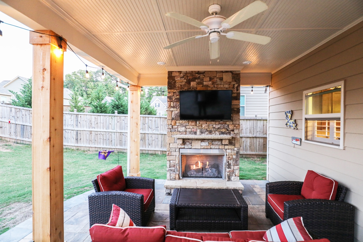 backyard outdoor living room with furniture, fan, and fireplace