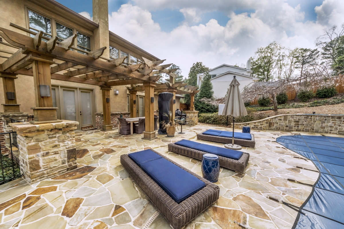hardscaped patio with covered pool and blue wicker lounge chairs