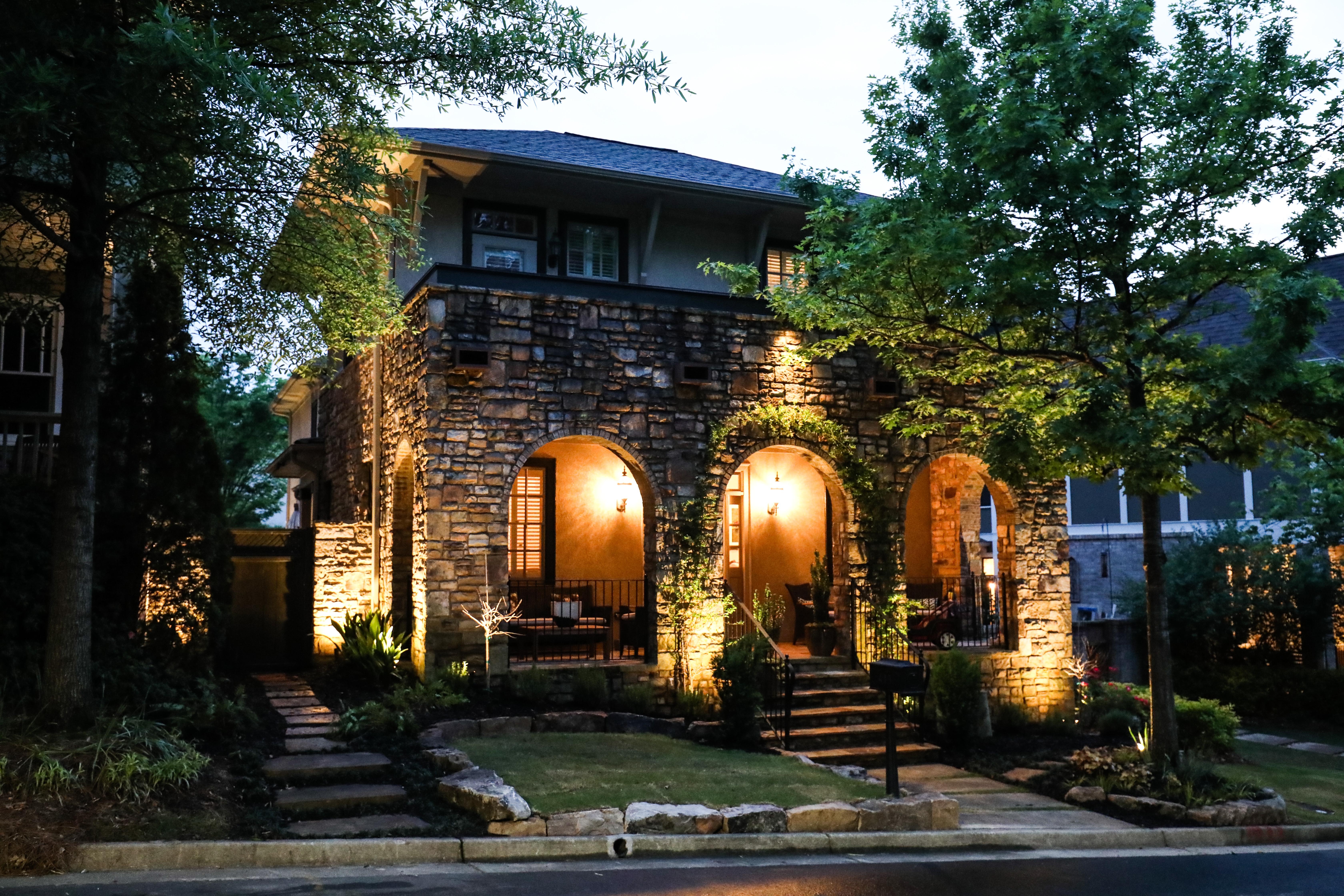 outdoor lighting on stone house with landscaping
