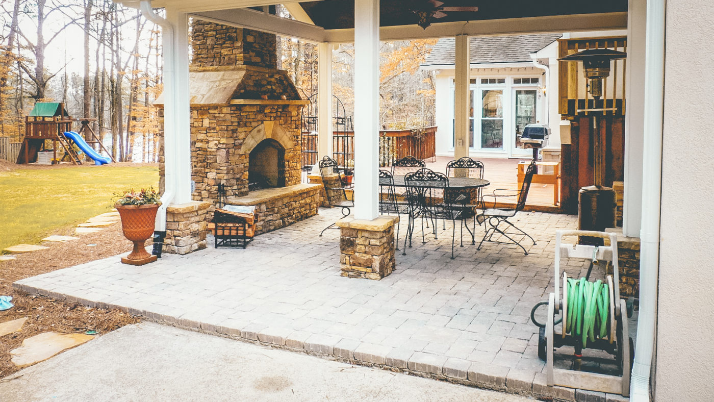 outdoor living room in backyard landscape with stone fire place