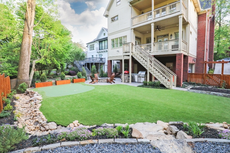 backyard patio living space with fire pit and putting green