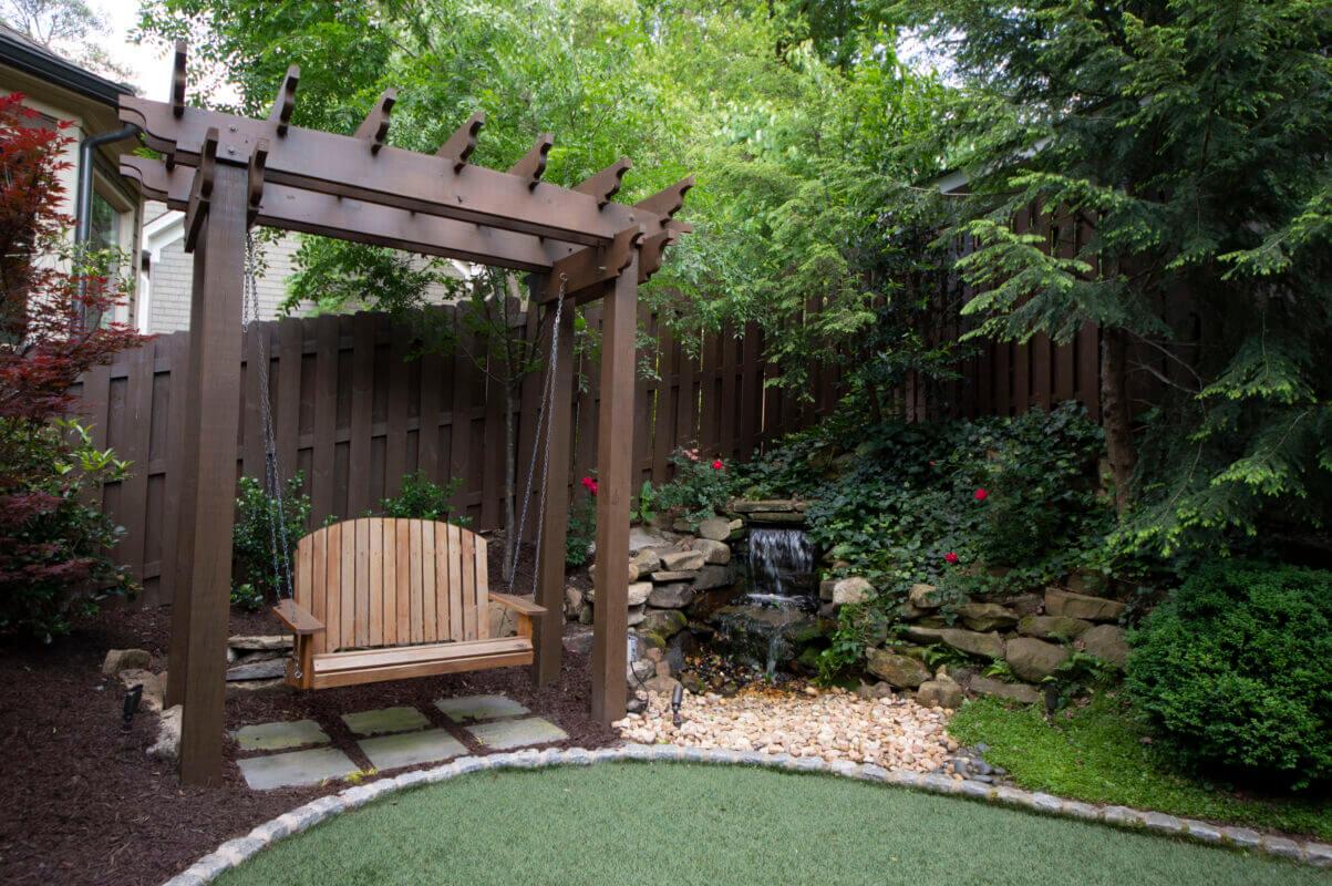 backyard swing hanging from arbor in designer backyard